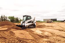 Bobcat T650 compact track loader pushes material on a building site with a bucket.