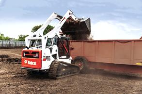 Bobcat compact track loader lifting and dumping dirt over truck bed wall.