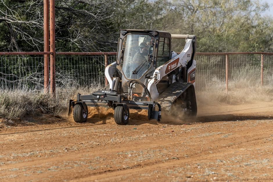 Operator Using T76 Compact Track Loader With Soil Conditioner Attachment To Pulverize The Soil Along Fence