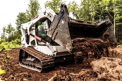 A Bobcat T770 compact track loader clears dirt and rock from a new building lot.