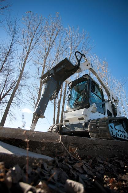 Bobcat T770 compact track loader is used to demolish a concrete sidewalk.