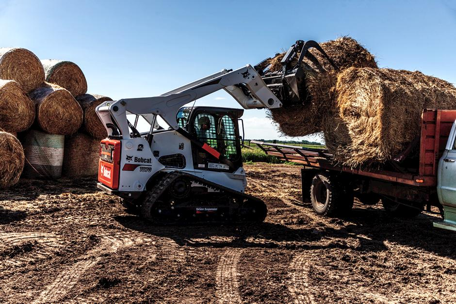 Bobcat T870 compact track loader and industrial grapple placing a round hay bale onto a flatbed truck.