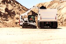 Bobcat T870 compact track loader and bucket attachment dumping materials over the sidewall of a truck.