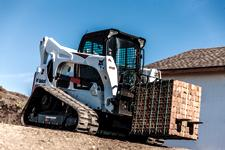 Bobcat T870 compact track loader and pallet fork attachment moving a load of bricks.