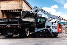 Bobcat T870 compact track loader dumping material into a truck with a bucket attachment.