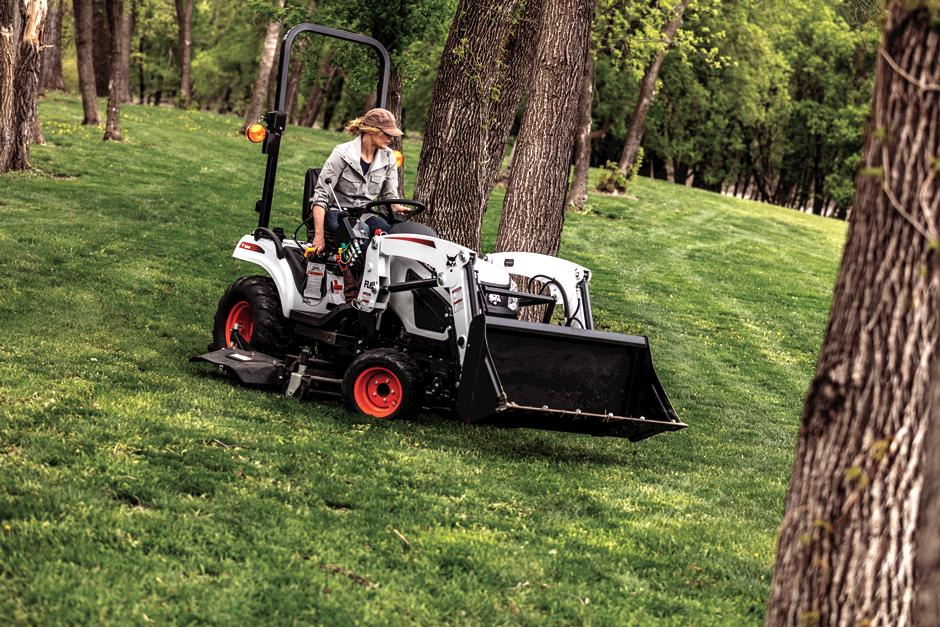Operator Mowing Around Trees Using Mid-Mount Mower On Compact Tractor