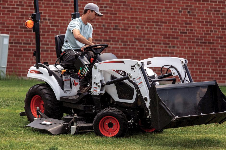 Operator Using A Mid-Mount Mower Attachment On A CT1025 To Mow Around Building