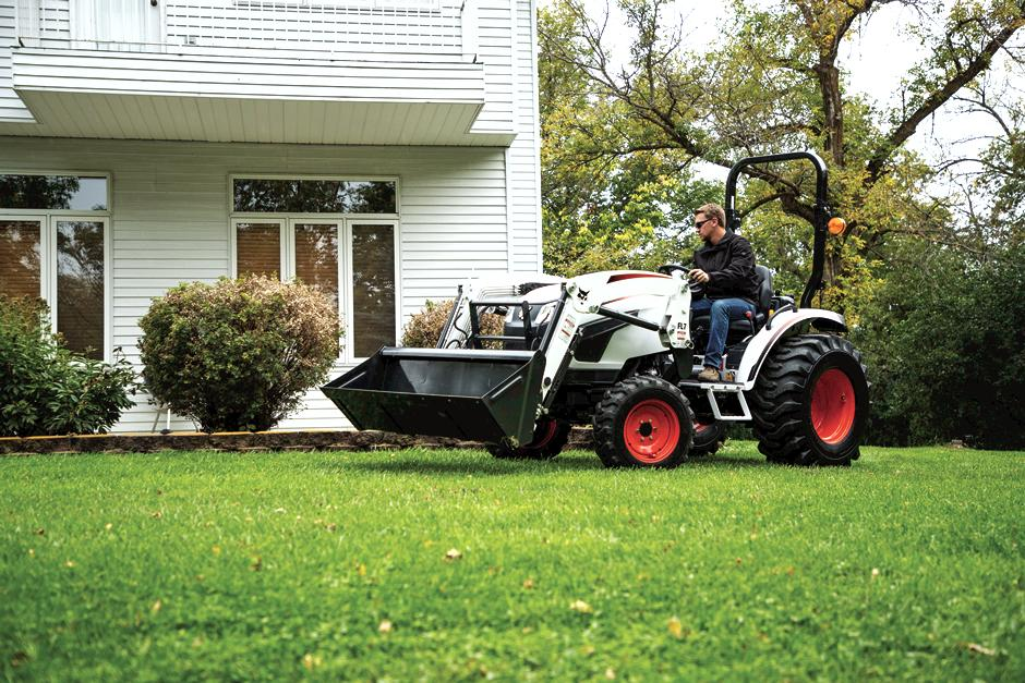 Homeowner Maneuvering Bobcat CT2025 Compact Tractor Around House On Acreage