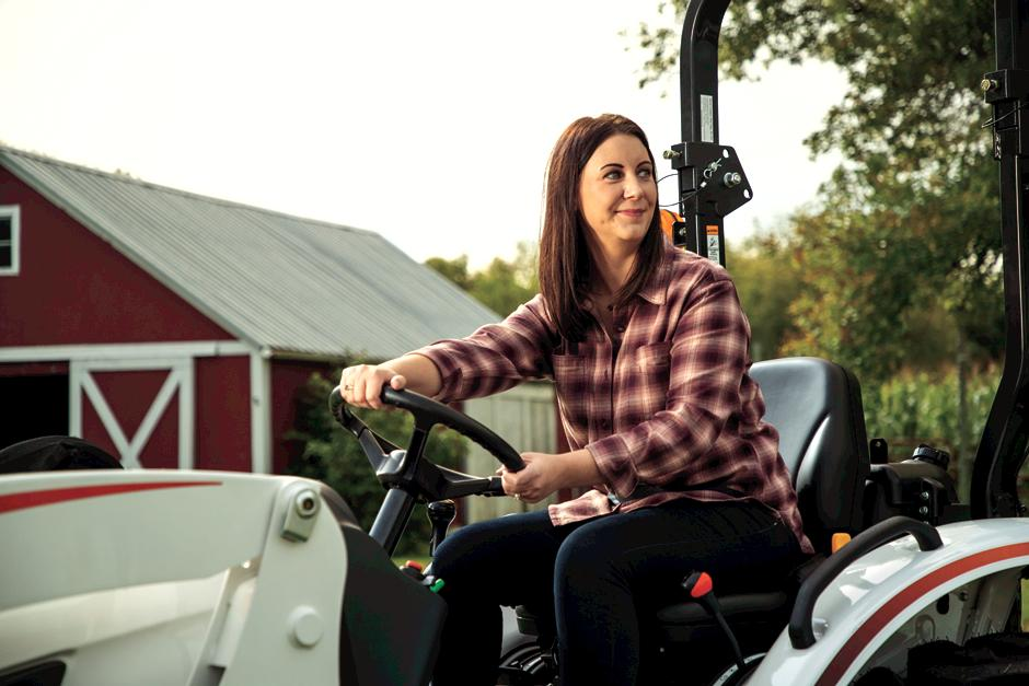 Operator In Red Plaid Shirt Driving A Bobcat CT2025 Compact Tractor On Her Acreage With Barn In the Background