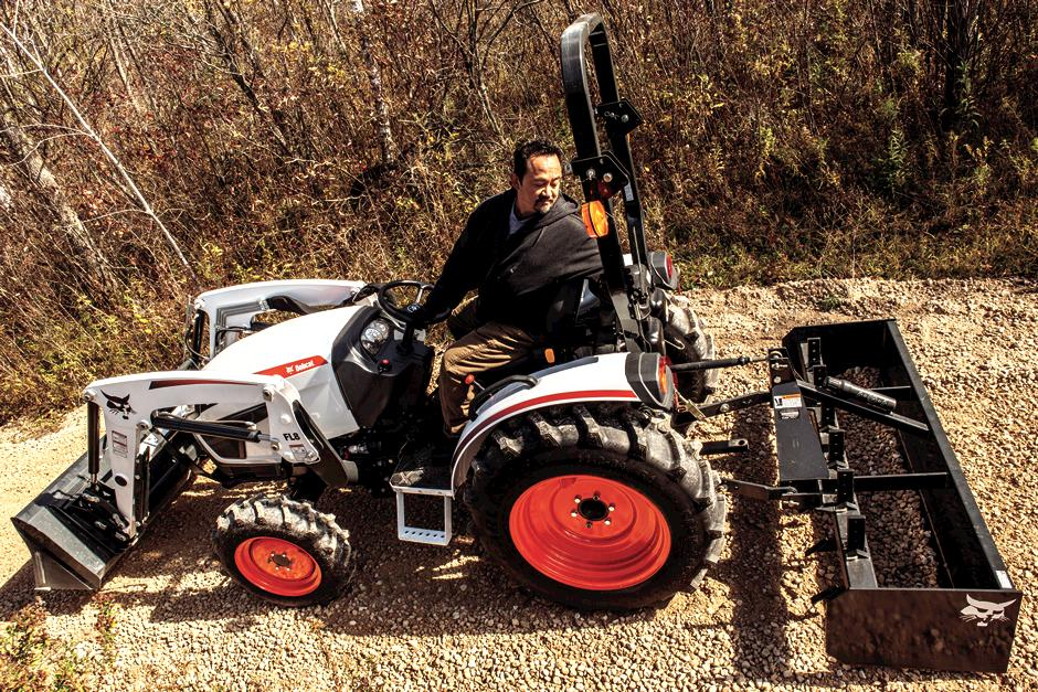 Operator Using Bobcat CT2040 Compact Tractor With Three-Point Tine Rake Attachment To Rake Land In Front Of Acreage
