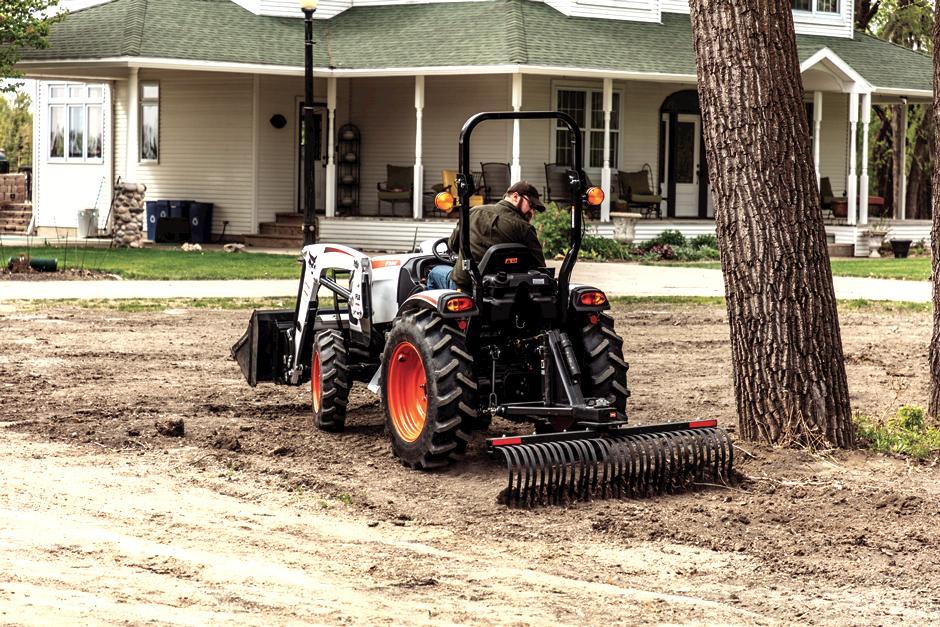 Operator Using Bobcat CT2040 Compact Tractor With Three-Point Tine Rake Attachment To Rake Ground Around Tree In Yard