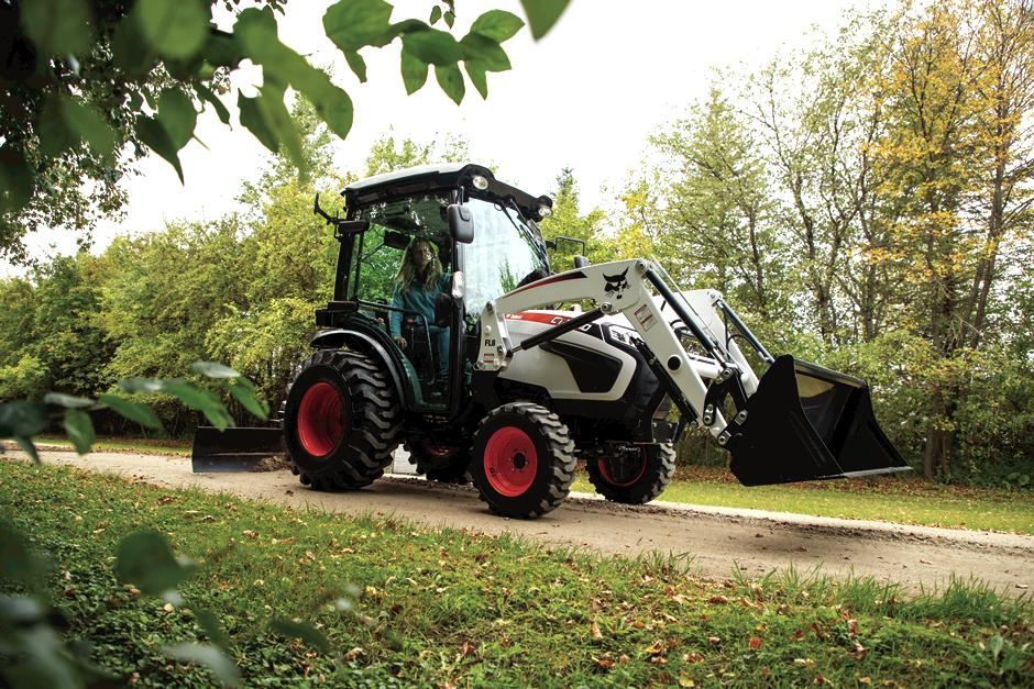 Bobcat CT2540 Compact Tractor With Three-Point Angle Blade And Bucket Attachment Driving Down Dirt Road