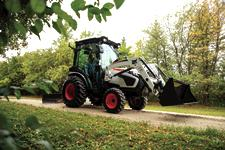 Farmer Drives Bobcat Compact Tractor Down Property's Gravel Driveway