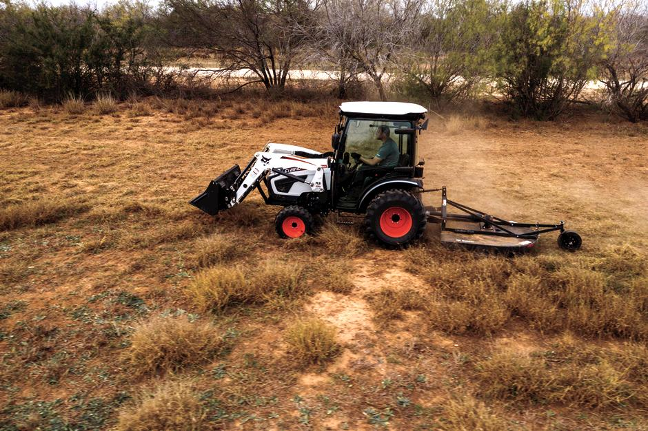 Farmer Drives Bobcat Compact Tractor With Front-End Loader And Rotary Cutter Attachments Through Field