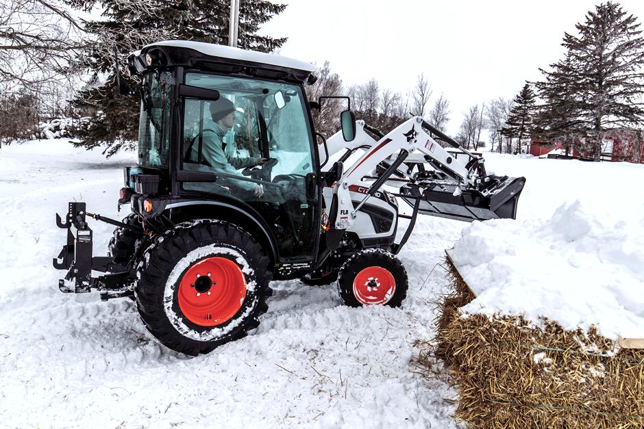 Operator Inside Enclosed Cab Of CT2540 Compact Tractor Moving Snow With Front-End Loader Attachment