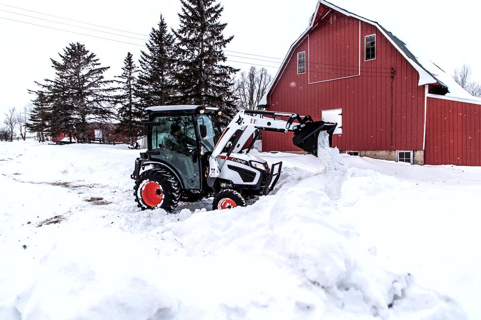 Homeowner Clears Driveway Of Snow With Front-End Loader Attachment On Compact Tractor