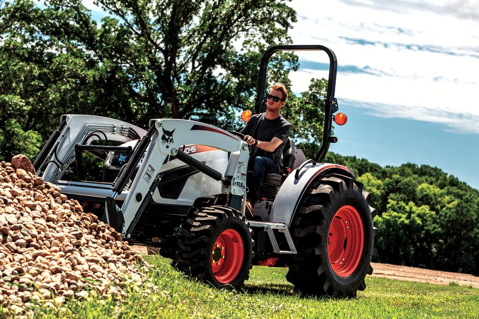 Bobcat compact tractor with front-end loader attachment moving material.