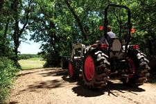 Homeowner Drives Compact Tractor Down Acreage Lane