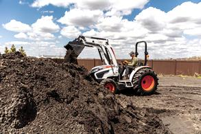 Landscaper Transports Dirt Using Front-End Loader Attachment On Bobcat Compact Tractor