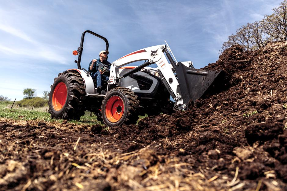 Farmer Uses Compact Tractor With Front-End Loader To Move Dirt From Pile