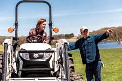 Property Owner Sitting In Open Cab Of Tractor Talking With Man Standing Next to Machine
