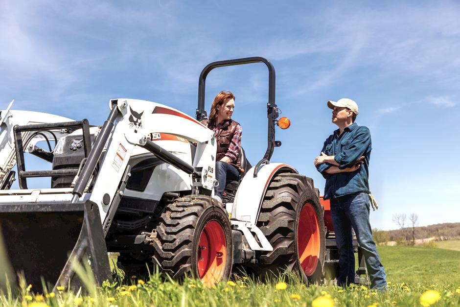 Acreage Owners Converse Between A Bobcat Compact Tractor With Front-End Loader Attachment In Open Field