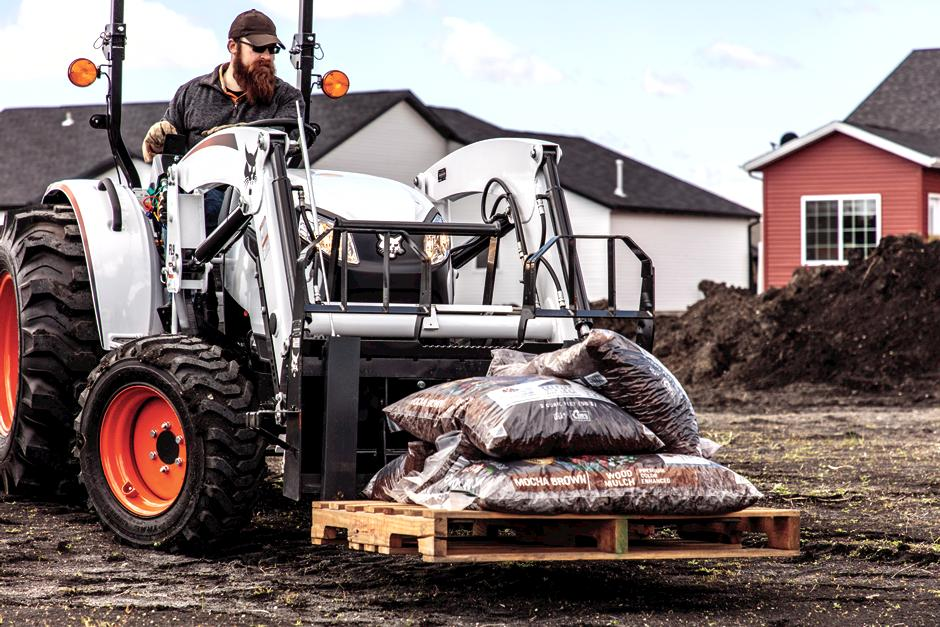 Landscaper Using Bobcat CT4050 Compact Tractor With Pallet Fork Attachment To Move Mulch On Acreage
