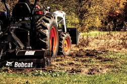 Close-Up Of Tires On Bobcat CT4058 Compact Tractor With Three-Point Tiller Implement To Cultivate Soil