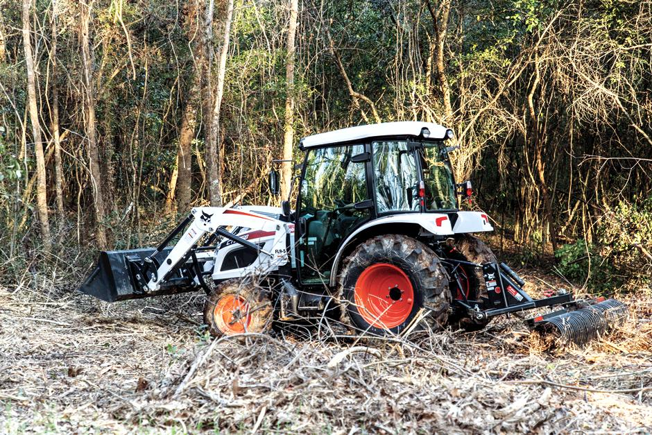 Operator Using A Bobcat CT5558 Compact Tractor With Three-Point Tine Rake Attachment To Rake Dead Limbs And Brush Along Tree Line