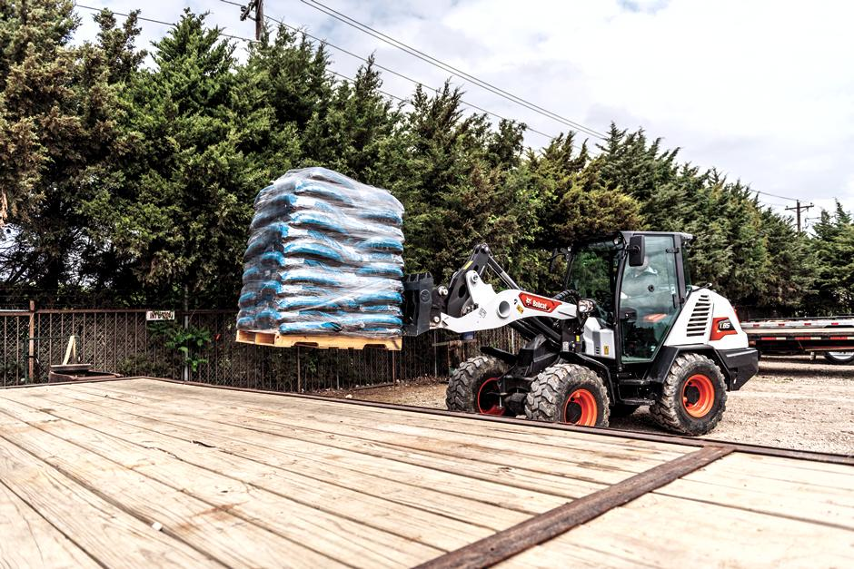 Bobcat L85 Compact Wheel Loader With Pallet Fork Attachment Moves Material On To Dock.