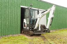 Bobcat E20 compact (mini) excavator moves through a narrow doorway.