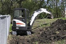 Bobcat E26 compact (mini) excavator has a minimal tail swing, allowing it to work close to this fence.