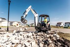 Bobcat R-Series E32 compact (mini) excavator with grapple attachment picking up rocks.