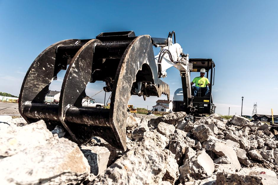 Construction Worker Using Bobcat E32 Compact Excavator With Grapple Attachment To Move Broken Concrete