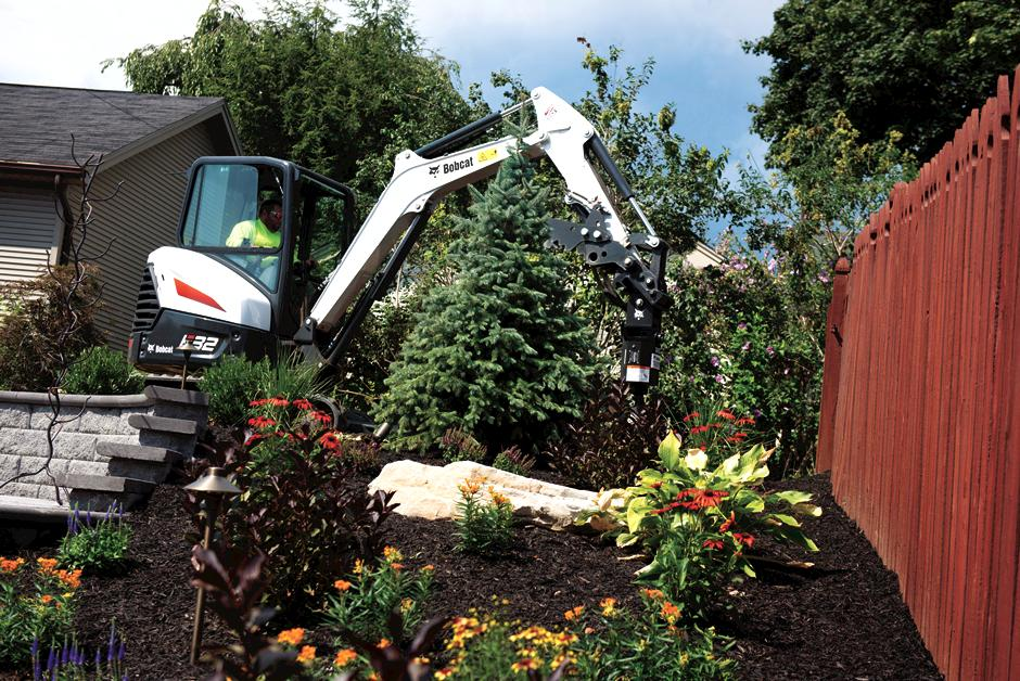 Landscaper Using Bobcat E32 Mini Excavator With Auger Attachment In Backyard Project