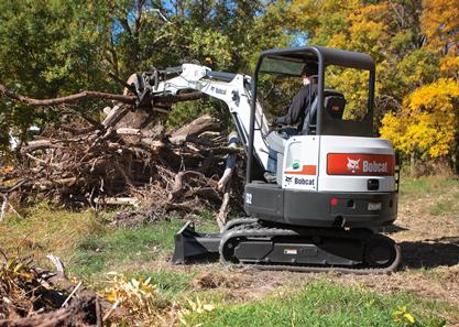 Bobcat E32 compact excavator (mini excavator) moves a pile of branches using the clamp attachment.