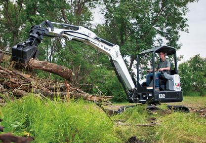 Bobcat E32 compact excavator (mini excavator) lifts large log with clamp attachment.