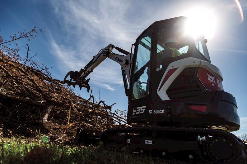 Bobcat R-Series E35 compact (mini) excavator clearing jobsite with three-tine grapple attachment.