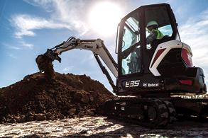 Compact excavator operator observes safe techniques on the jobsite