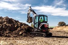 Bobcat E35 compact (mini) excavator lifting a load of black dirt