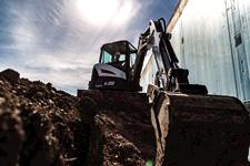 Bobcat E35 compact (mini) excavator and bucket attachment digging inside a trench.