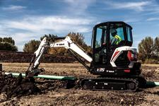 Bobcat E35 compact (mini) excavator and bucket attachment digging a trench.