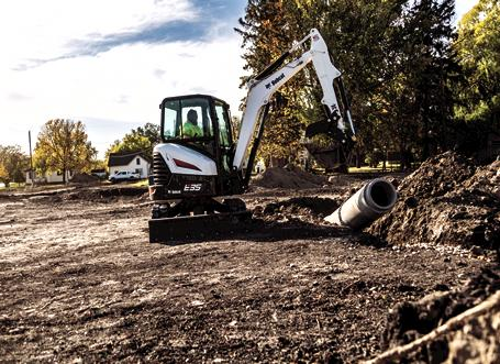 Construction Worker Using Bobcat E35 Mini Excavator With Clamp Attachment To Move Concrete Pipe On Jobsite