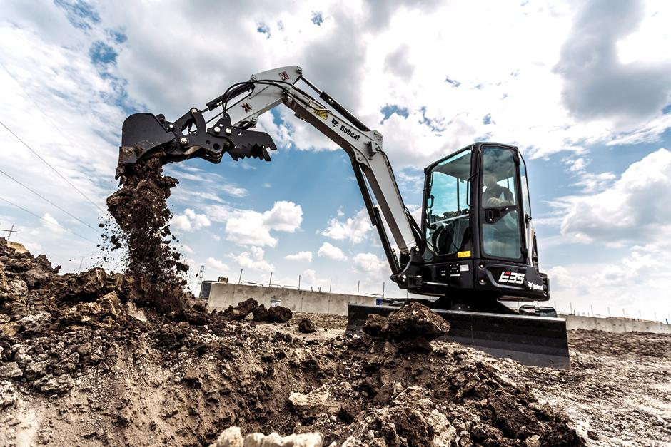 Operator Uses Bobcat E35 Mini Excavator With Bucket Attachment To Move Earth On Construction Jobsite