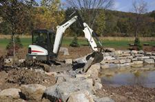 Bobcat E35 compact excavator lifting with a bucket and clamp attachment.