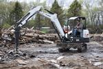 Bobcat E42 excavator demolishing concrete with a breaker attachment.
