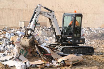 Clamp (thumb) attachment on the Bobcat E45 compact excavator lifts rubbish in a waste facility.