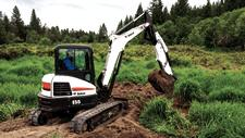 Bobcat E55 compact (mini) excavator with an extendable arm and bucket attachment removing dirt from a hole.