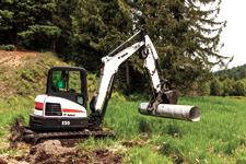 Bobcat E55 compact (mini) track loader and grapple attachment moving a metal culvert.