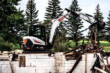 Operator Using Bobcat E60 Compact Excavator With Extendable Arm And Hydraulic Clamp Attachment To Move Debris From Demolition